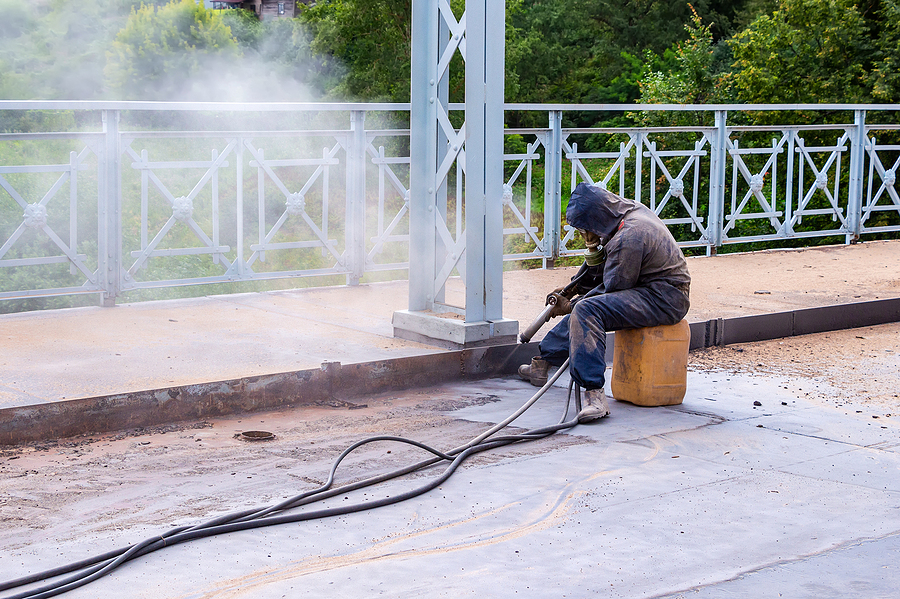 Worker with protective mask works a bridge with sandblast.
