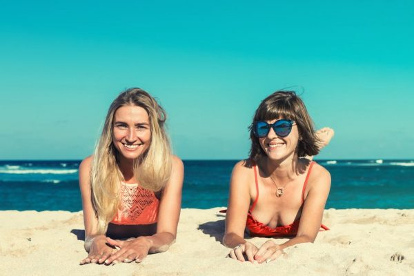 Two woman lying on the sand wearing designer bathing suits