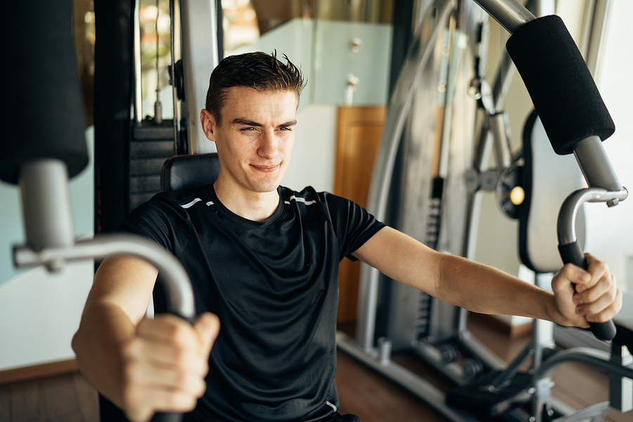 Man doing a chest press using an exercise equipment