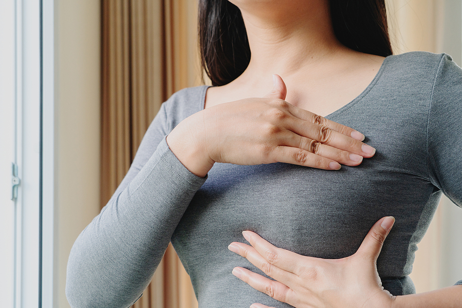 Woman checking her breast for lumps