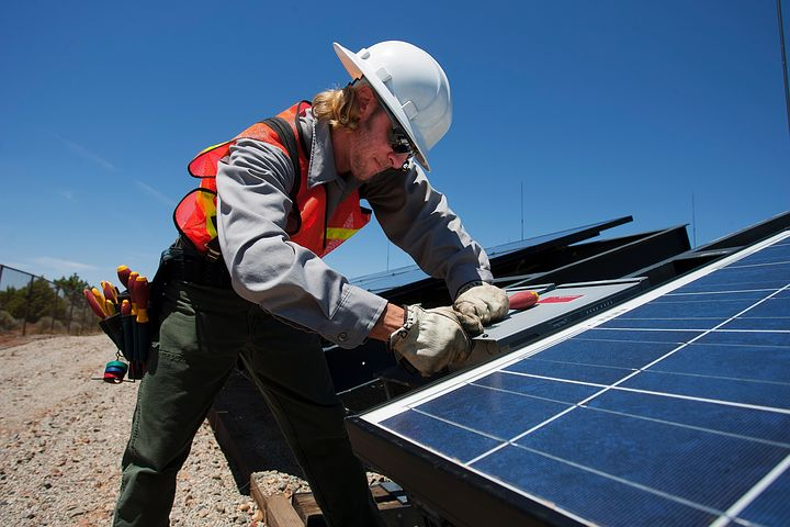Worker installing commercial solar panel in the roof