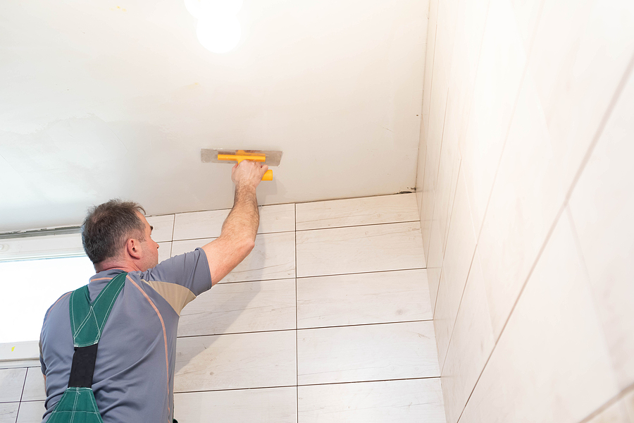 Worker applies plaster on the ceiling for a complete bathroom renovation