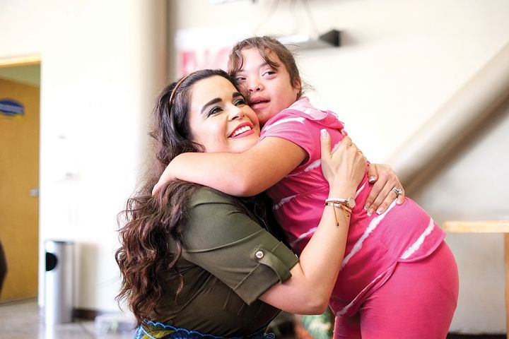 NDIS female worker hugging a woman with down syndrome